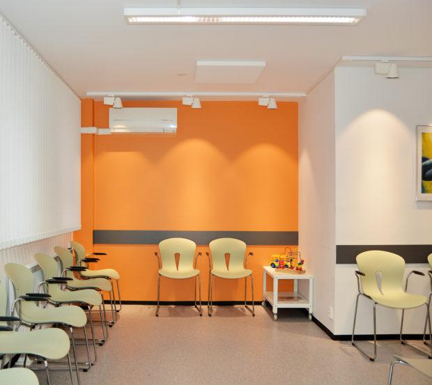 Orange vegg og lyse grønne stoler.