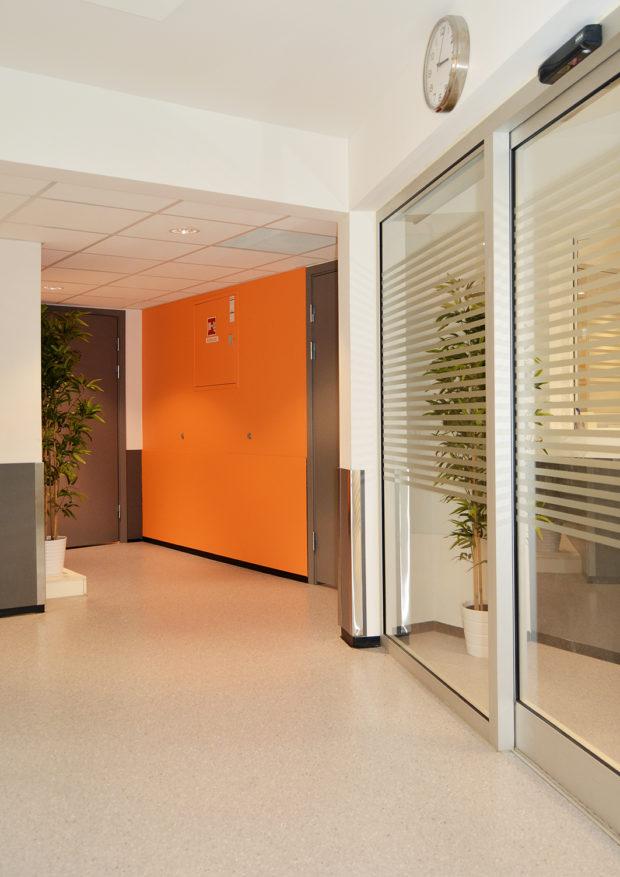 Orange kontrastvegg og glassdører.